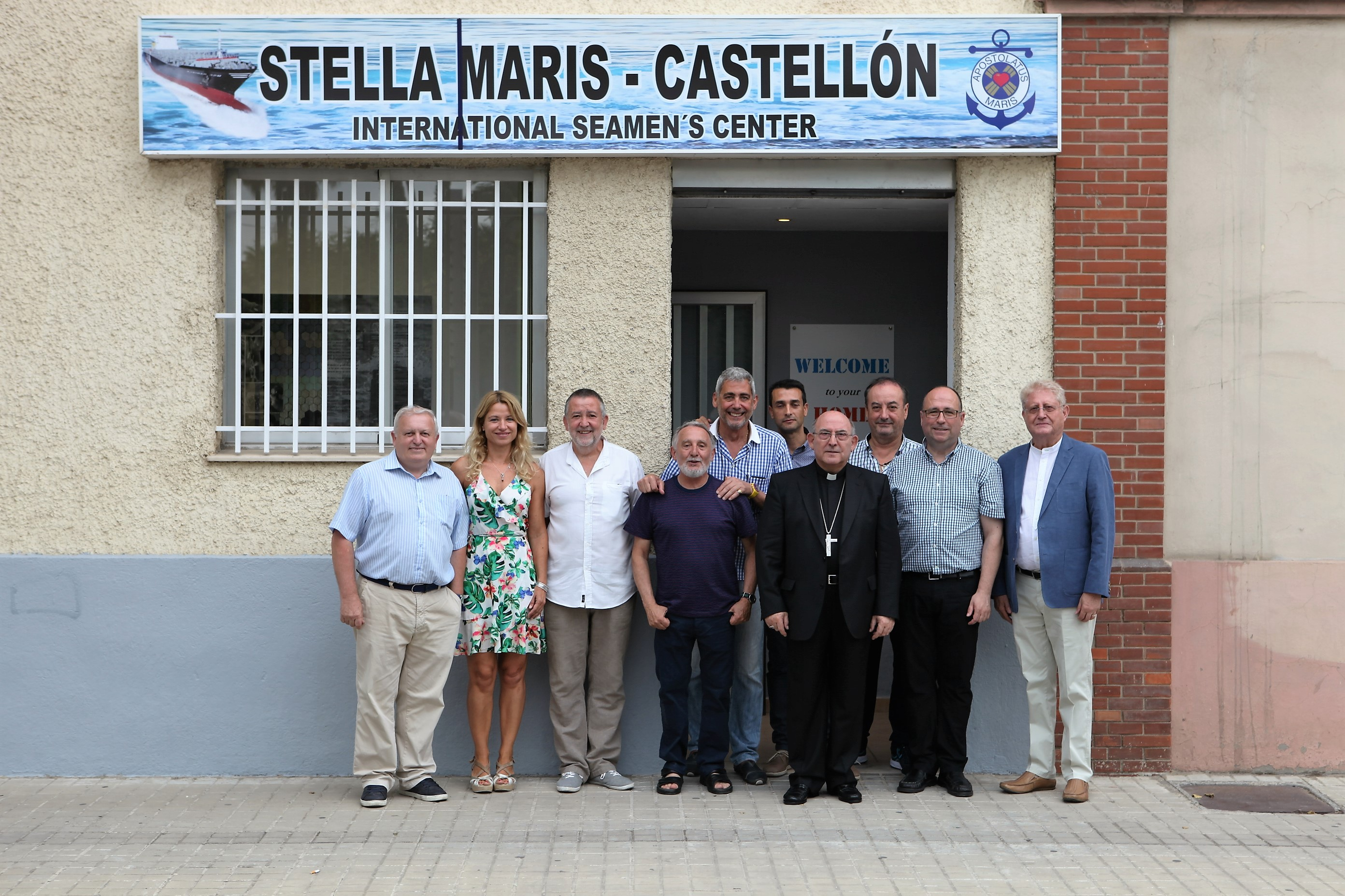 Imagen de voluntarios con el Obispo castellonense en el exterior del local